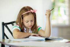 Child doing homework. Kids read and write. Cute little girl doing homework, reading book, coloring pages, writing and painting. Children paint. Kids draw. Child royalty free stock image