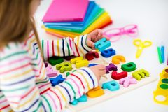 Child doing homework for school. Kids learn and paint. Child doing homework for school at white desk. Wooden educational abc toy puzzle for kids. Happy back to royalty free stock photography