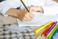 Child doing homework and writing story essay. Elementary or primary school class. Closeup of hands and colorful pencils stock photo