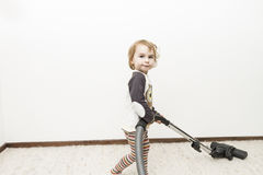 Child doing household chore. Cute child doing household chore with vacuum cleaner stock image