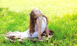 Child doing yoga exercise stretching on grass in sunny summer Royalty Free Stock Photography