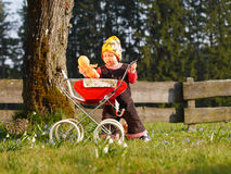 Child with doll carriage. Child playing with doll carriage Royalty Free Stock Photo