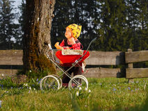 Child with doll carriage. Child playing with doll carriage Royalty Free Stock Images