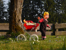 Child with doll carriage. Child playing with doll carriage Stock Images