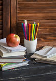 Child domestic workplace and accessories for training and education - books, notebooks, notepads, colored pencils, pens, rulers. And a fresh red apple stock images