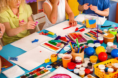 Child dough play in school. Plasticine for children. Mold from plasticine in kindergarten . Cropped of kids knead modeling clay with hands in preschool Royalty Free Stock Photos
