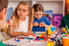 Child dough play in school. Plasticine for children. Mold from plasticine in kindergarten .Kids knead modeling clay with hands in preschool. Preparing for a Royalty Free Stock Image