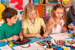Child dough play in school. Plasticine for children. Mold from plasticine in kindergarten . Kids knead modeling clay with hands in preschool. Children`s Stock Photography