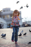 Child and doves. Child playing with doves in the city street stock photos