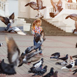 Child and doves. Child playing with doves in the city street Royalty Free Stock Image