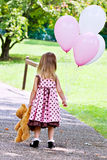 Child Dragging Teddy Bear and Holding Balloons Stock Photography