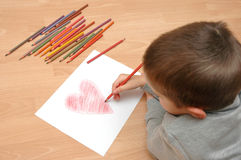 Child draw heart on paper stock images