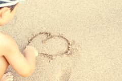 Child draw heart on sand. Summer vacation concept stock images