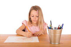 Child draw a picture. Child draw a pretty picture on a wooden table. Isolated on a white background Stock Photo
