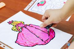 Child draw a woman. Child drawing picture outdoors in summer stock photo