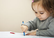 Child drawing. Portrait of a two years old girl drawing a picture with a blue crayon Royalty Free Stock Images