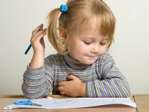 Child drawing. Young pretty girl teach draw with blue pen Royalty Free Stock Photos