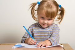 Child drawing. Young pretty girl learn drawing with blue pen Stock Photo