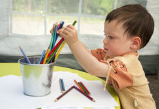 Child drawing. Portrait of a small child, boy or girl, drawing picture and playing with crayons royalty free stock image