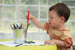 Child drawing. Portrait of a small child, boy or girl, drawing picture and playing with crayons royalty free stock photography