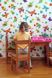 Child drawing. Little girl with long hair sitting at desk and drawing in her children room with butterfly wallpapers Stock Image