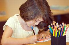 Child drawing. Child colouring in a drawing with colourful pencils