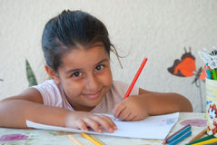 Child drawing 2. Child coloring in a drawing with colorful pencils royalty free stock images