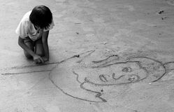 Child Drawing. A child blind in one eye draws outside the temple of Preah Kahn in Siem Reap Cambodia Stock Image