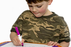 Child drawing. Young child drawing at a table with markers Stock Photos