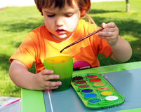 Child drawing. Child painting with brush and watercolors Royalty Free Stock Photography