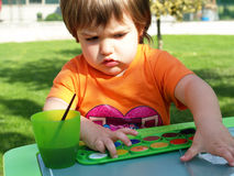 Child drawing. Child painting with brush and watercolors Royalty Free Stock Images