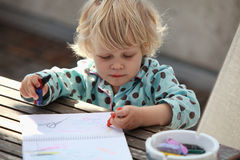 Child drawing an abstract picture. A blond Caucasian girl child  drawing an abstract picture with a  crayons  at a table in the backyard Royalty Free Stock Photography