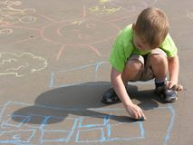 Child drawing on asphalt Royalty Free Stock Photos