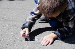 Child drawing on asphalt in spring, child paint crayons Stock Images