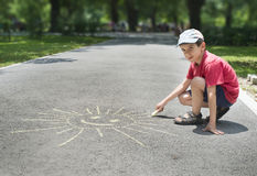 Child drawing on asphalt. Child drawing sun on asphalt in a park stock photography