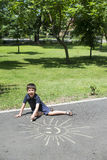 Child drawing on asphalt Stock Images