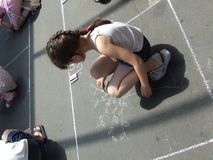 Child drawing on the asphalt w Royalty Free Stock Image