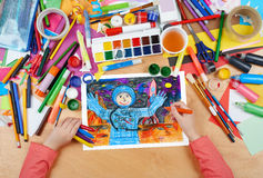 Child drawing astronaut exploring the red planet, space concept, top view hands with pencil painting picture on paper, artwork. Workplace stock photography