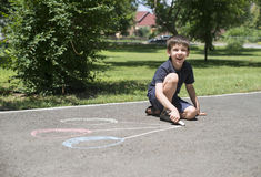 Child drawing balloons on asphalt. In a park royalty free stock photo