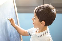 Child drawing on blackboard royalty free stock images
