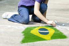 Child drawing Brazil`s flag. On the ground royalty free stock photo