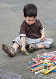 Child drawing with chalk. A small child, boy or girl, drawing on a asphalt road or pavement with a chalk royalty free stock photos