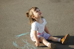 The child drawing a chalk on asphalt Stock Images