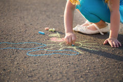 Child drawing a chalk on asphalt Royalty Free Stock Photos