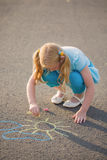 Child drawing a chalk on asphalt Stock Photography