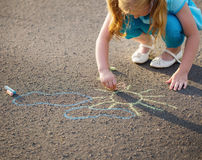 child drawing a chalk on asphalt Stock Images