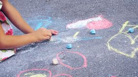 The child drawing a chalk on asphalt. Child drawings paintings on asphalt concept. The child drawing a chalk on asphalt stock photography