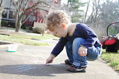 Child Drawing with Chalk Outside. Child, toddler boy drawing with chalk on a sidewalk outdoors, outside stock photo