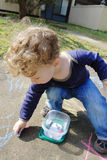 Child Drawing with Chalk Outside. Child, toddler boy drawing with chalk on a sidewalk Stock Photography