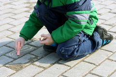 The child drawing with chalk on the pavement. Royalty Free Stock Images